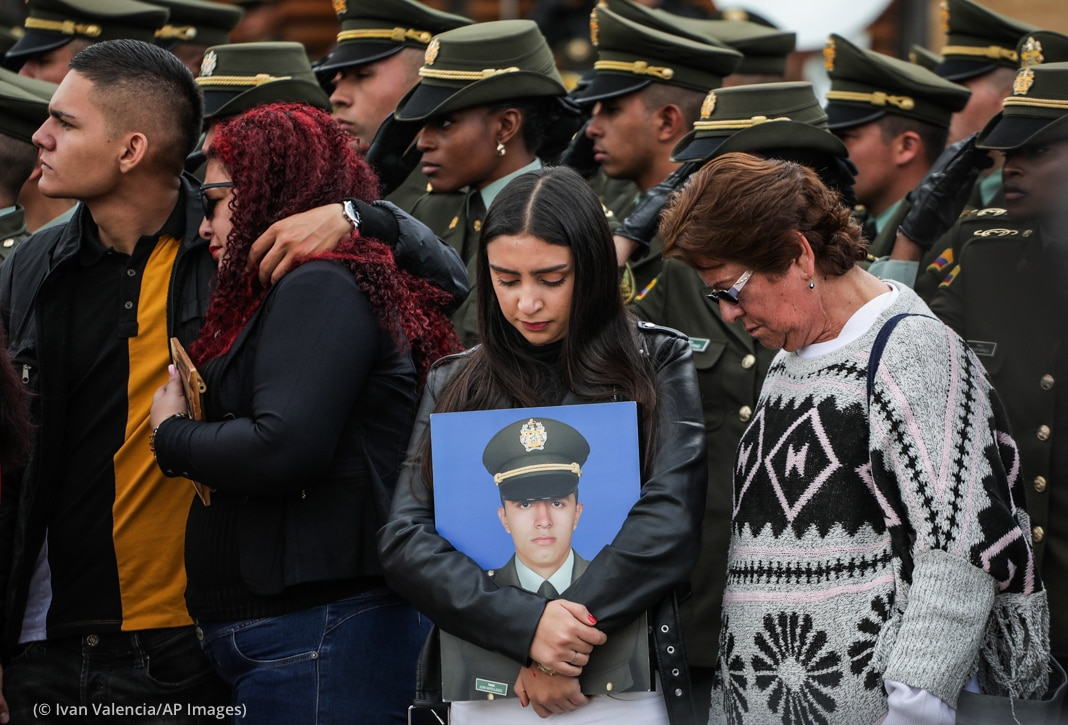 Woman in crowd holding portrait of uniformed man (© Ivan Valencia/AP Images)