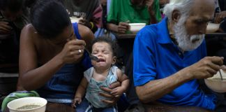 Woman feeding baby next to white-haired man eating (© Ariana Cubillos/AP Images)