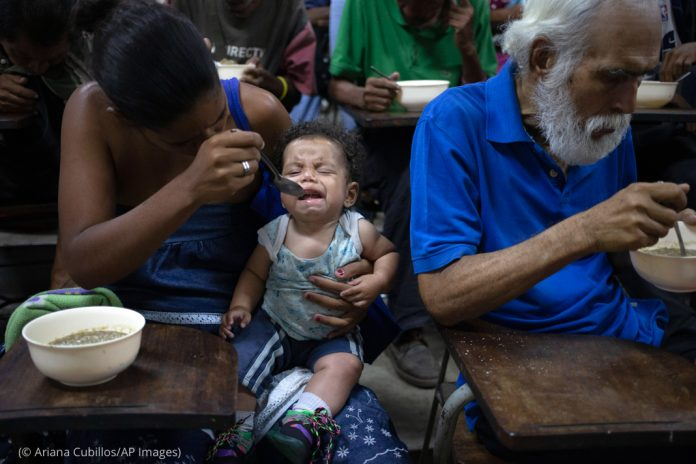 Woman feeding her baby next to a man eating (© Ariana Cubillos/AP Images)