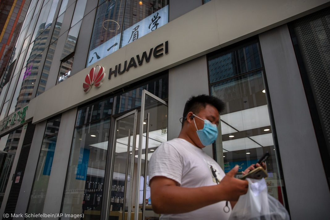Man looking at this phone while passing by Huawei store (© Mark Schiefelbein/AP Images)