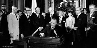 لنڈن جانس کرسی پر بیٹھے ایک دستاویز پر دستخط کر رہے ہیں اور اُن کے لوگ اردگرد کھڑے ہیں (© AP Images)