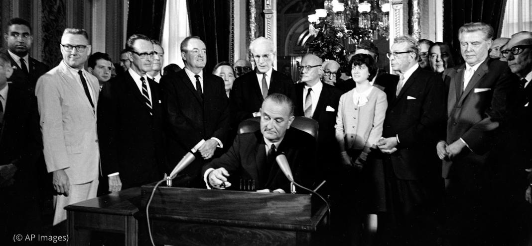 Lyndon Johnson assis à un bureau et en train de signer un document, et tout un groupe de personnes derrière lui (© AP Images)