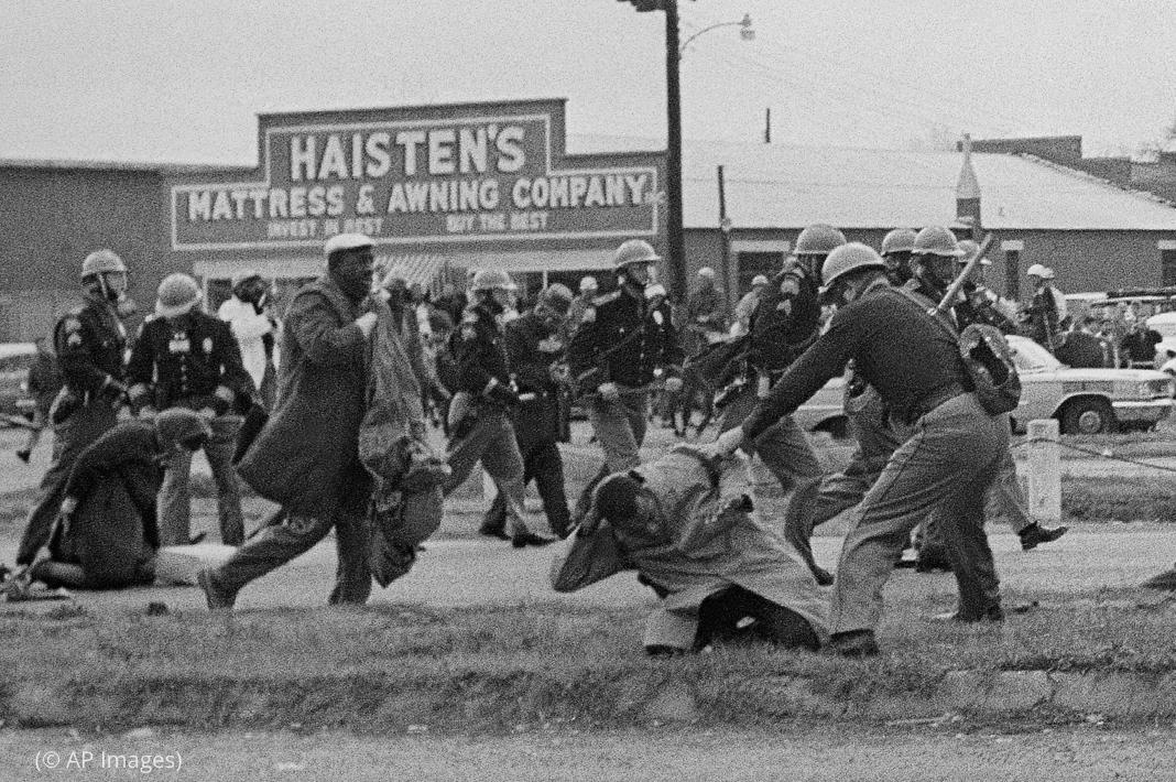 Uniformed, helmeted men beating people in street (© AP Images)