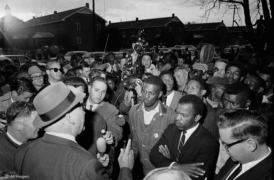 Des hommes entourés de journalistes et face à un homme qui parle dans un microphone (© AP Images)