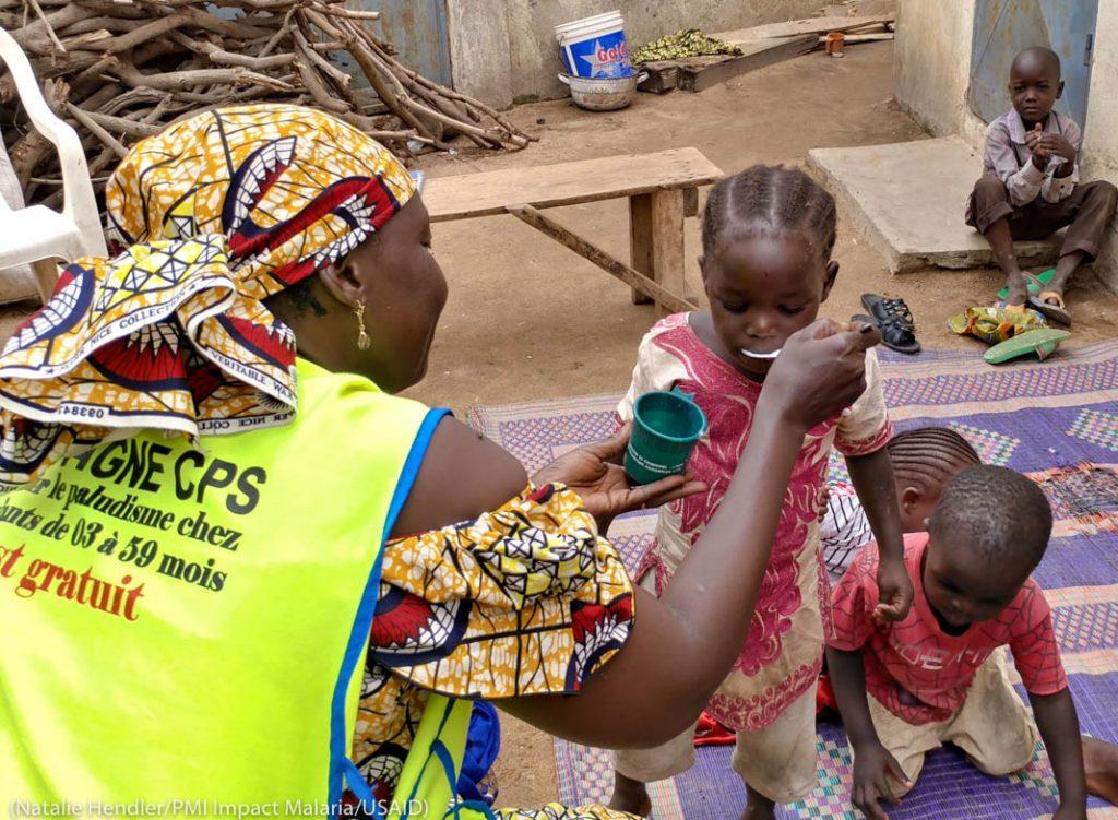 Сотрудник кормит детей с ложки (Natalie Hendler/PMI Impact Malaria/USAID