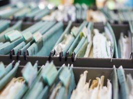 Filing cabinets full of file folders holding paper