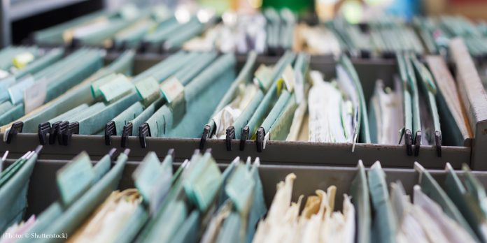 Filing cabinet drawers full of file folders holding paper (© Shutterstock)