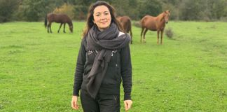 Une femme debout dans un champ avec des chevaux en arrière-plan (Photo offerte par Rena Alimardanova)