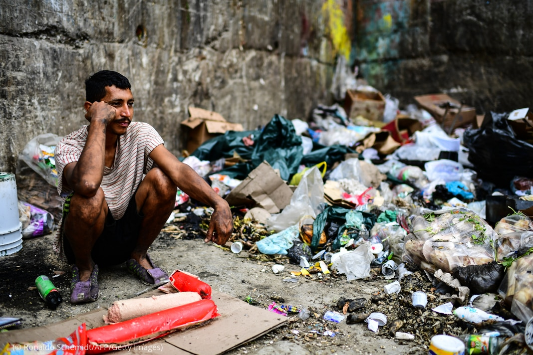 Man sitting amid trash and garbage (© Ronaldo Schemidt/AFP/Getty Images)
