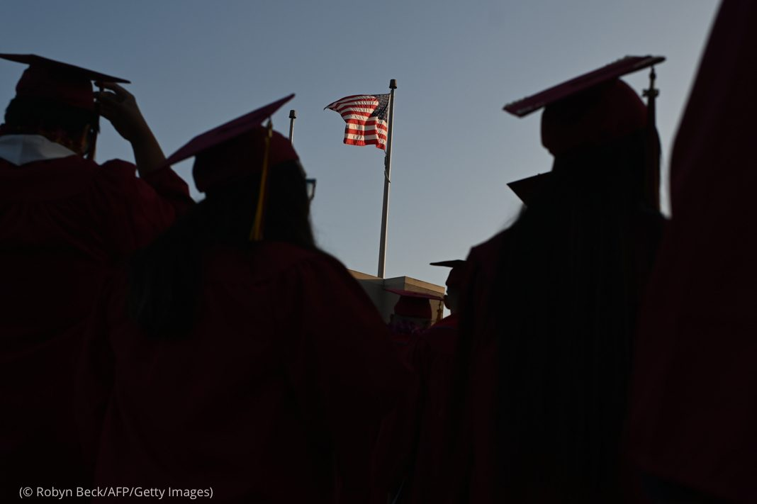 Silhouettes of students in caps and gowns with U.S. flag in background (© Robyn Beck/AFP/Getty Images)