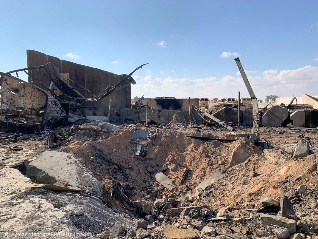 بمباری سے پڑنے والا ایک گڑھا اور عمارتوں کو پہنچنے والا نقصان (© Ayman Henna/AFP/Getty Images)