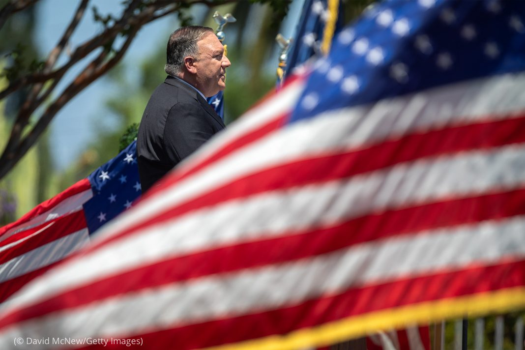 Michael R. Pompeo surrounded by U.S. flags while speaking (© David McNew/Getty Images)