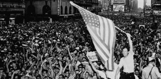 Man waving U.S. flag in huge crowd in New York City streets (© Universal History Archive/Universal Images Group/Getty Images)