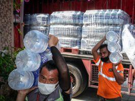 Sejumlah pria mengangkut botol air besar dari truk (© The Coca-Cola Company)