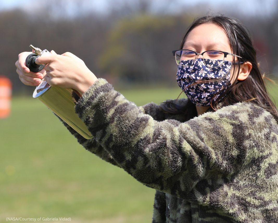 Une jeune femme avec un masque de protection tenant un récipient (NASA/Photo offerte par Gabriela Vidad)