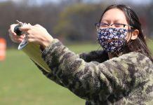 Wanita bermasker memegang tabung (NASA/Foto milik Gabriela Vidad)