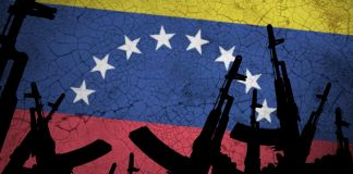 وینیزویلا کے پرچم کی نمائندگی کرنے والے پس منظر میں دکھائی گئیں بندوقیں (© Anton Watman/Shutterstock)