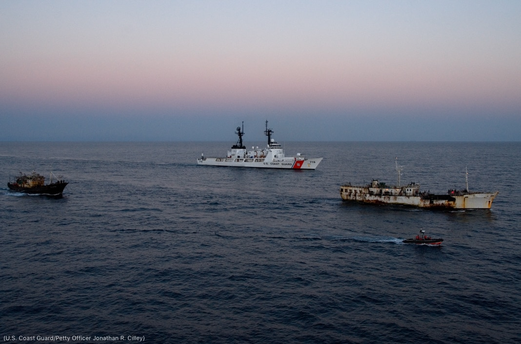 U.S. Coast Guard cutter sailing near two fishing vessels, with a response boat in foreground (U.S. Coast Guard/Petty Officer Jonathan R. Cilley)