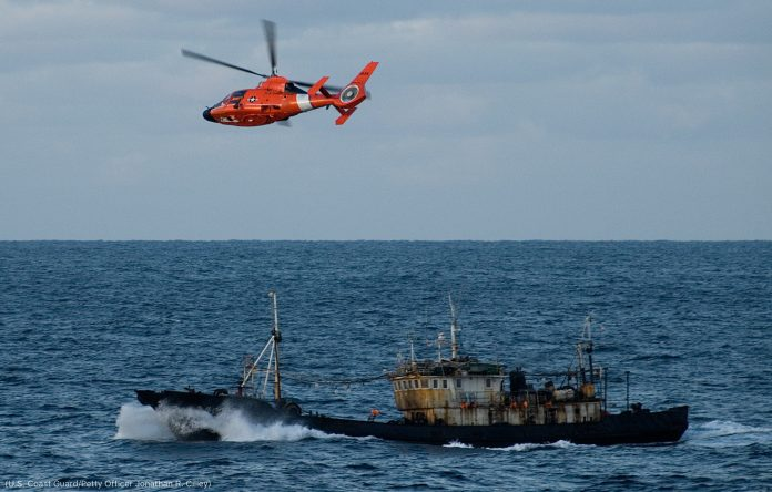U.S. Coast Guard helicopter flying over a fishing vessel (U.S. Coast Guard/Petty Officer Jonathan R. Cilley)