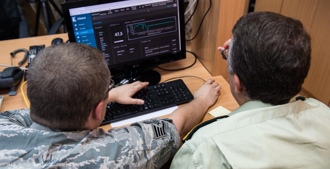 Dos hombres en uniforme trabajando en la pantalla de una computadora (Ejército de EE. UU./especialista Craig Jensen)