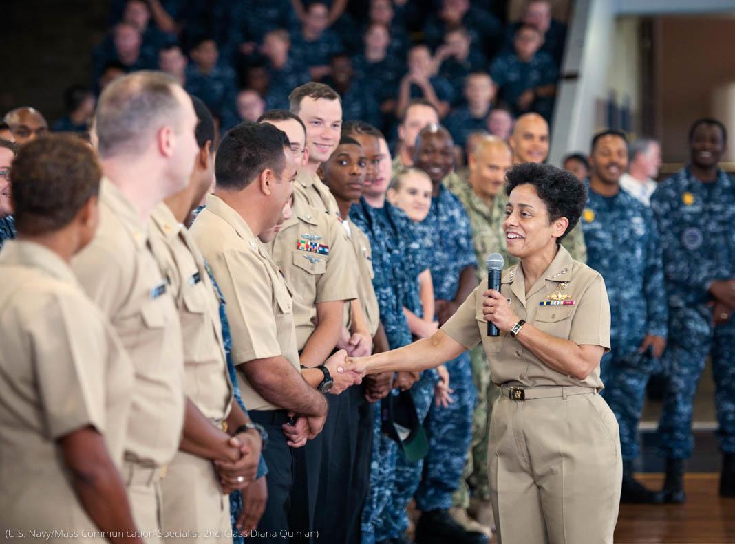 Laksamana wanita berjabat tangan dengan anggota lain yang berdiri berjajar dalam barisan (AL AS/Spesialis Komunikasi Massa Kelas 2 Diana Quinlan)