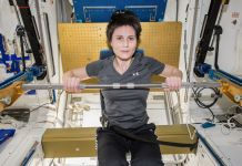 Wanita sedang duduk dan berolahraga dengan batang besi di ruangan kecil (NASA)