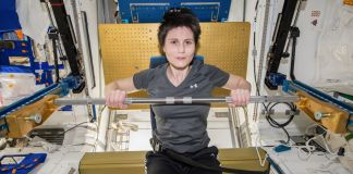 Woman seated and exercising with bar in small space (NASA)