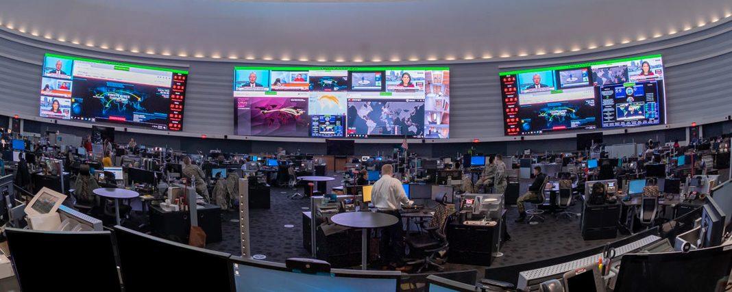 Tampilan melebar dari ruang bundar berukuran besar dengan para staf di meja dan konter, dengan layar berukuran besar di dinding (NSA)