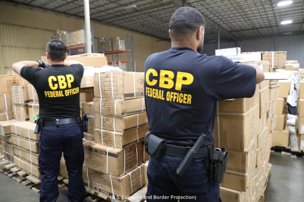 Des agents du CBP en uniforme en train d'inspecter des cartons (CBP)