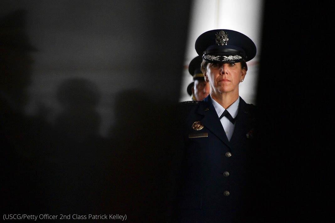 Une femme en uniforme s'avançant entre deux rideaux qui s'écartent (USCG/Petty Officer 2nd Class Patrick Kelley)