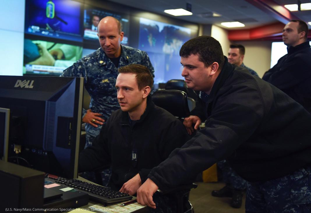 Sejumlah pria berseragam berdiri mengelilingi seorang pria yang duduk di depan komputer (U.S. Navy/Mass Communication Specialist 1st Class Samuel Souvannason)