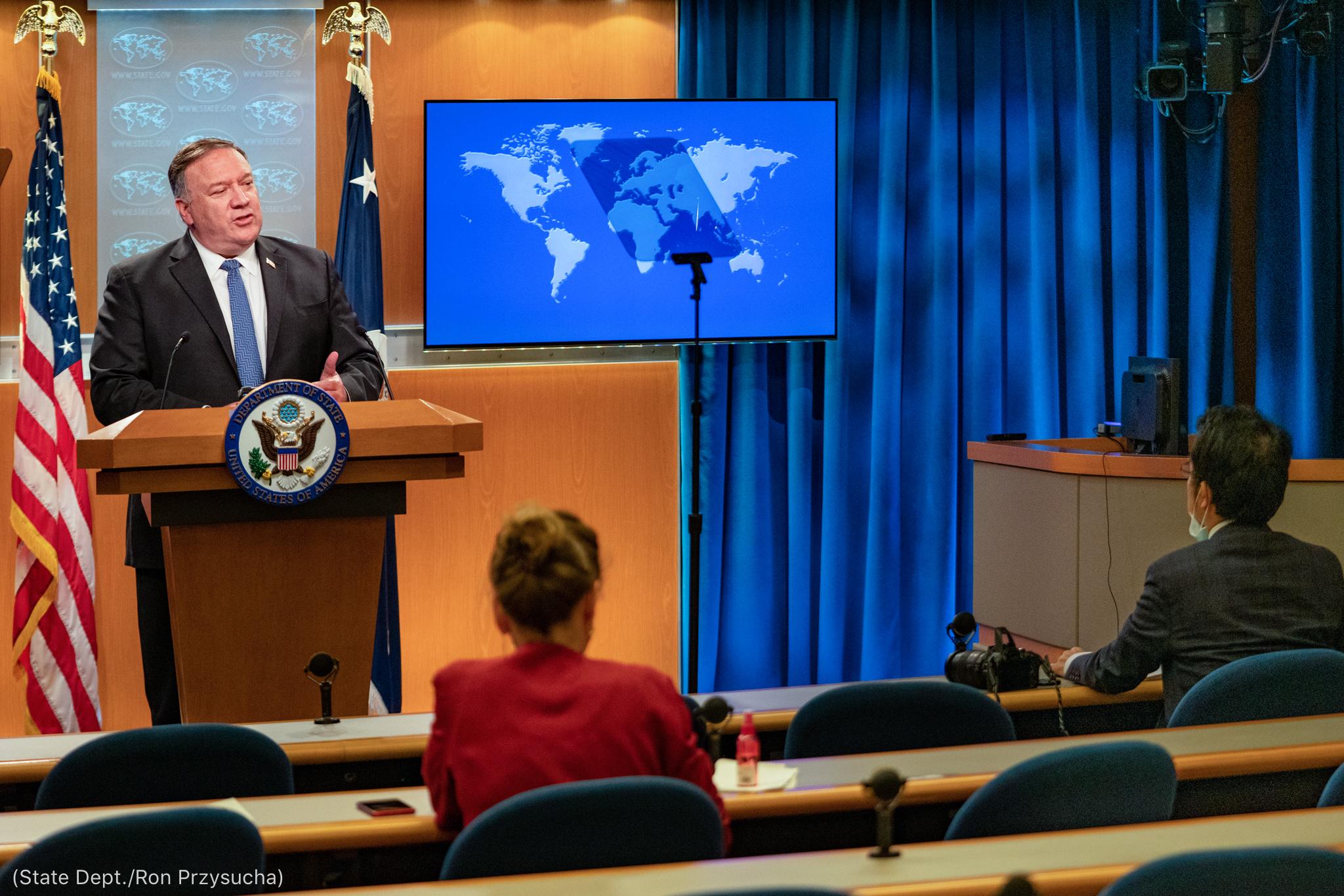 سٹیج پر وزیر خارجہ پومپیو تقریر کر رہے ہیں اور دو بیٹھے ہوئے فرد سن رہے ہیں (State Dept./Ron Przysucha)