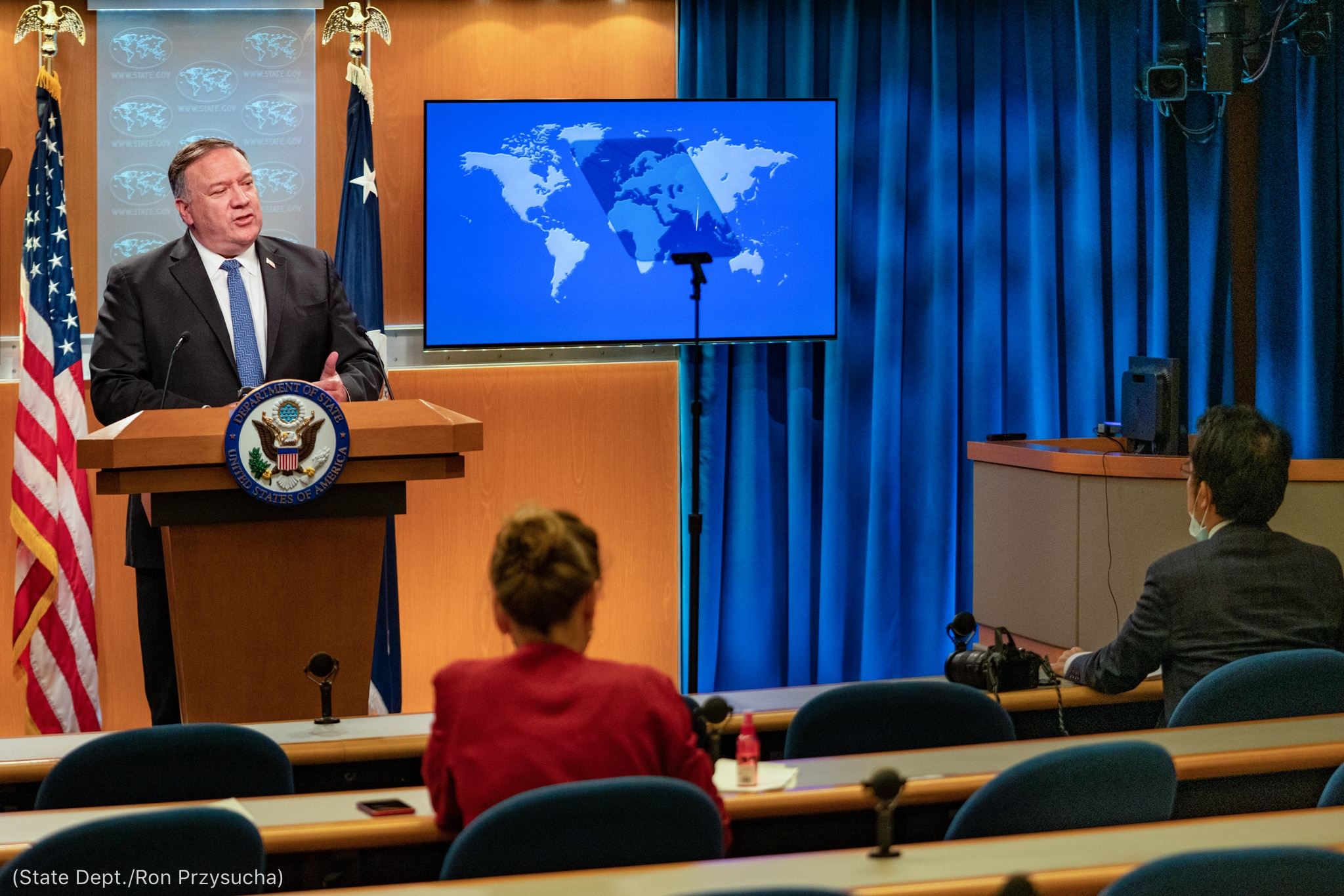 Michael R. Pompeo speaking behind lectern while two seated people listen (State Dept./Ron Przysucha)
