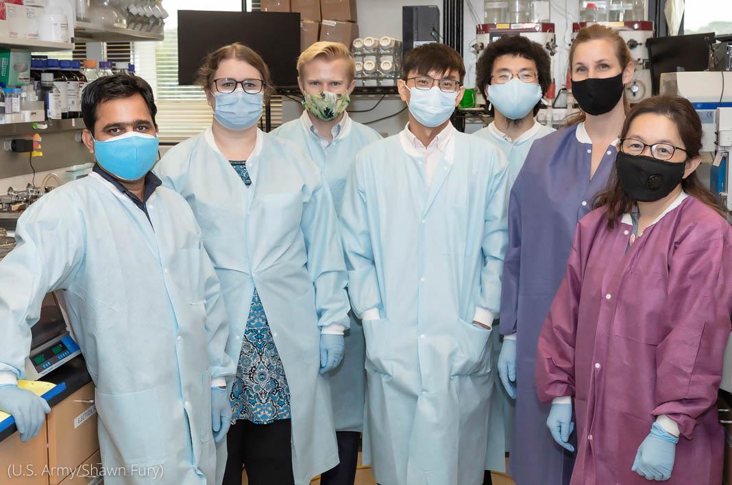 Un groupe de sept personnes, hommes et femmes, en tenue de protection posant pour la photo dans un laboratoire (U.S. Army/Shawn Fury)