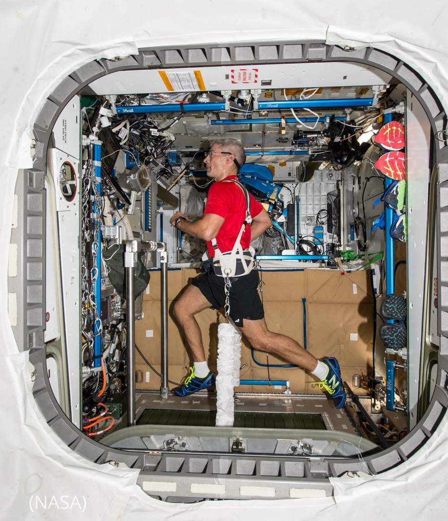 Man in shorts and T-shirt running on treadmill in small space (NASA)