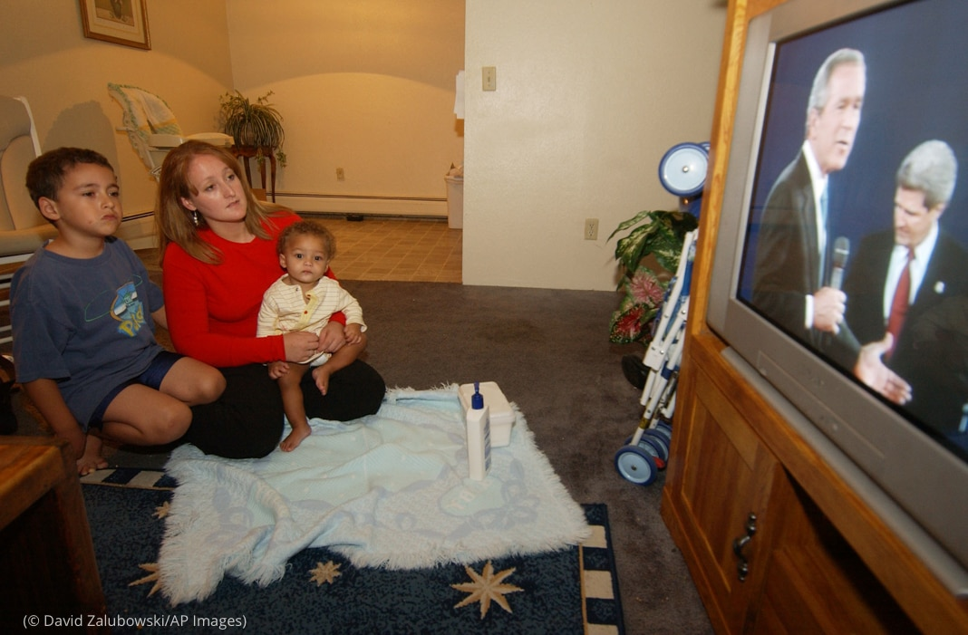 Woman with infant and boy on floor watching television (© David Zalubowski/AP Images)