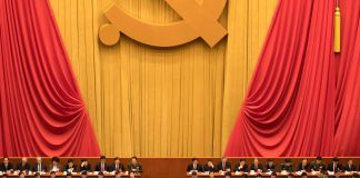 Officials sitting under yellow and red curtains with a large hammer and sickle decoration at the Chinese Communist Party congress (© Ng Han Guan/AP Images)