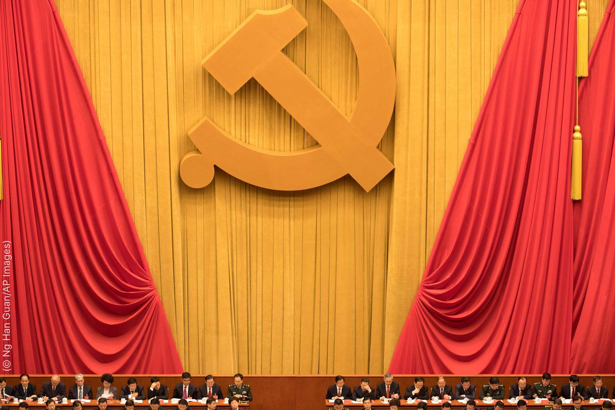 أشخاص جالسون وفوقهم مجموعة ستائر على إحداها رسم كبير لشعار المطرقة والمنجل. (© Ng Han Guan/AP Images)