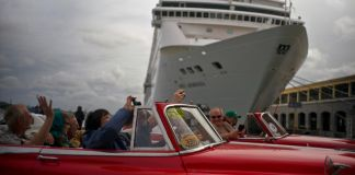 Tourists on two classic automobiles taking pictures in front of a cruise ship (© Ramon Espinosa/AP Images)