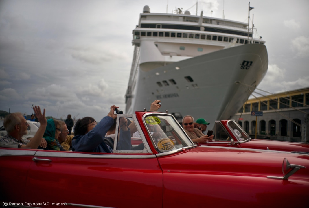 People in two red classic convertibles raising arms to take pictures in front of cruise ship (© Ramon Espinosa/AP Images)