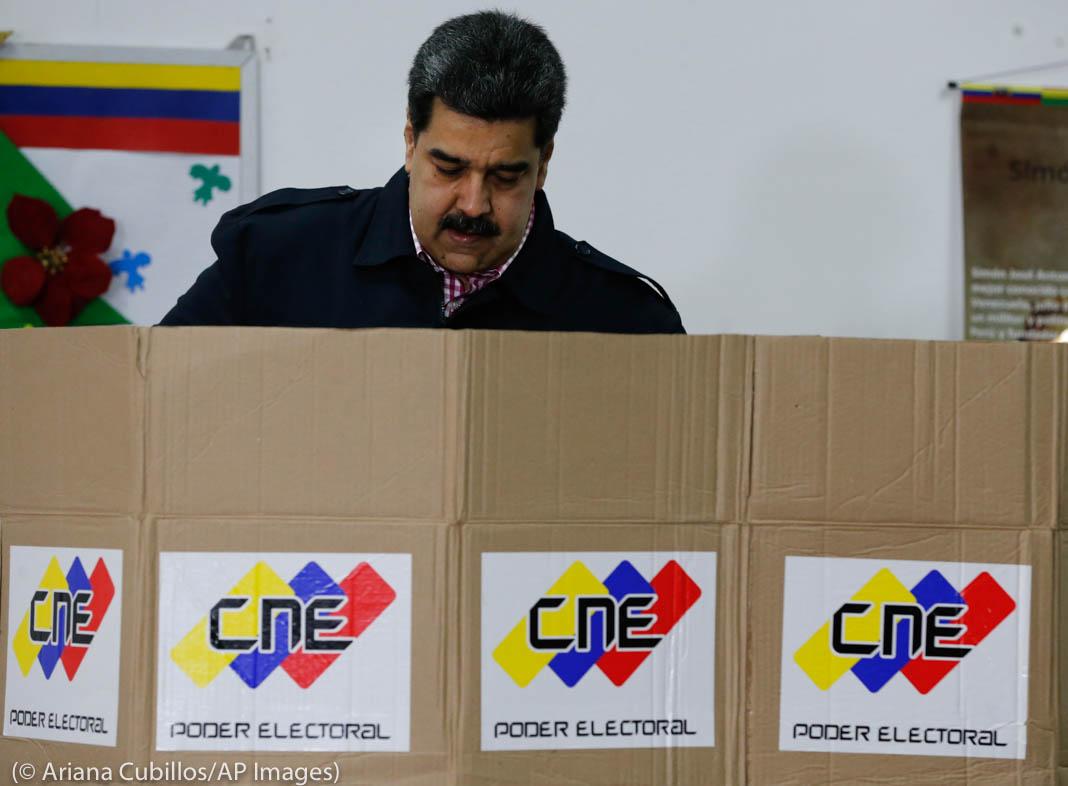 Nicolás Maduro voting behind cardboard barrier (© Ariana Cubillos/ AP Images)