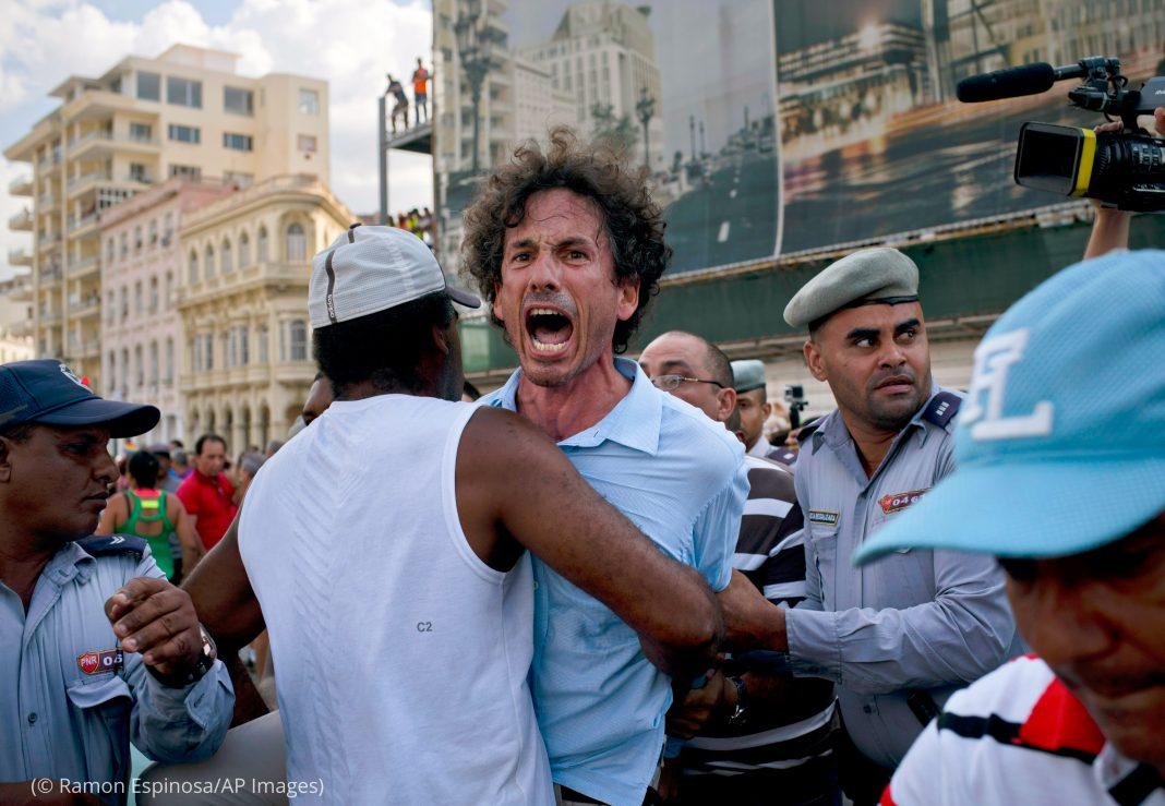 Dans une rue, des hommes en train de tenir les bras d'une personne qui crie (© Ramon Espinosa/AP Images)