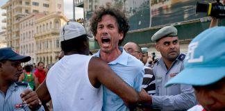 Pessoas seguram os braços de um homem que grita na rua (© Ramon Espinosa/AP Images)