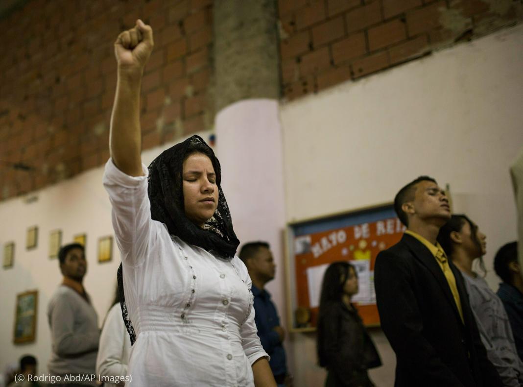آنکھیں بند کیے ہوئے ایک عورت ہوا میں اپنا ہاتھ بلند کیے ہوئے ہے (© Rodrigo Abd/AP Images)