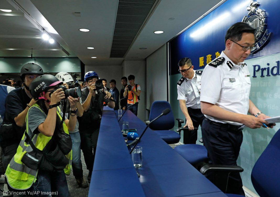 News photographers wearing helmets photograph police commissioner at news conference (© Vincent Yu/AP Images)