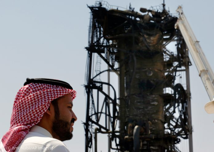 A man with a Saudi headdress standing in front of burnt and damaged tower (© Amr Nabil/AP Images)