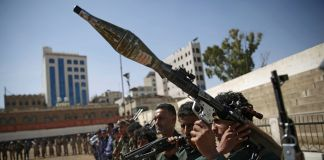 Fila de hombres sosteniendo armas (© Hani Mohammed/AP Images)