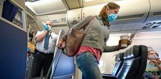 Penumpang mengenakan masker berjalan menyusuri lorong pesawat (© David J. Phillip/AP Images)