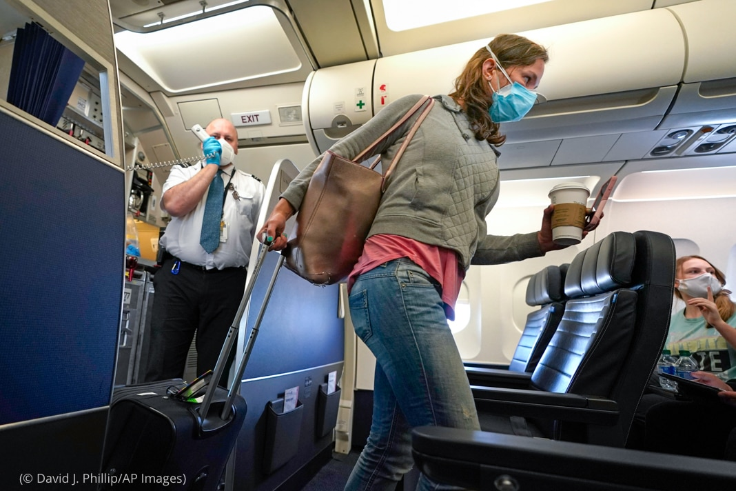 Person wearing mask and walking down aircraft aisle (© David J. Phillip/AP Images)