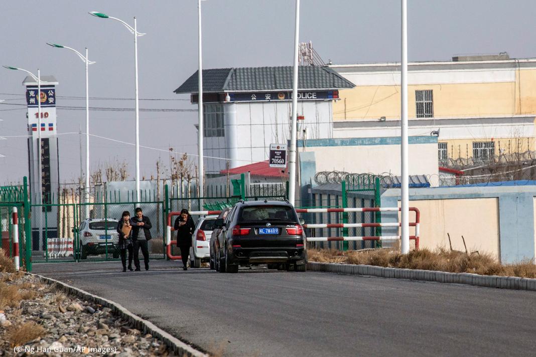 Büyük kapılı ve korunaklı tesisin dışında bekleyen arabalar ve insanlar (© Ng Han Guan/AP Images)
